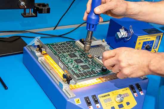 Precision Zone Technician de-soldering a PCB